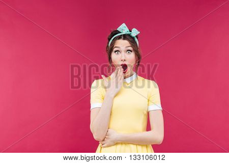 Amazed pretty pinup girl in yellow dress standing with mouth opened over pink background