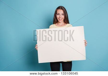 Pretty young woman holding empty blank board isolated on the blue background