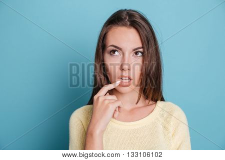 Close-up portrait of a pensive thougtful pretty girl thinking about something isolated on the blue background