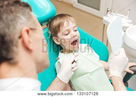 Cute little boy visiting dentist for teeth checkup in dental clinic