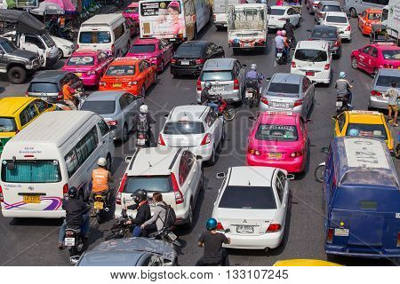 BANGKOK THAILAND - JANUARY 22 2015: Traffic moves slowly along a busy road in Bangkok Thailand. Annually an estimated 150000 new cars join the already heavily congested streets of Bangkok.