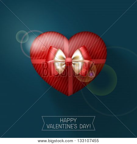 Red gift heart-shaped box tied with ribbons and decorated with bow on dark background. Congratulations to Happy Valentine's day below