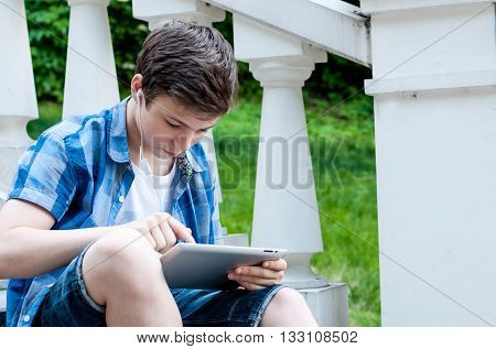 carried away by teenager with a tablet sitting on the stairs