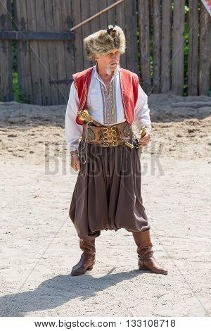 KHORTYTSYA UKRAINE - JUNE 22: Cossack festival at the Zaporozhye Sech at June 22 2013 in island Khortytsya Ukraine. Traditional clothes of Cossack.