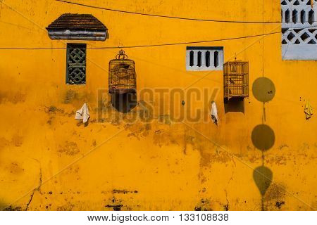 Yellow wall with small windows and bird cages. Hoi An, Vietnam