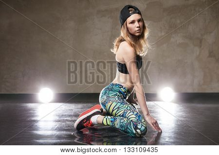 Portrait of stylish street dancer looking at camera. Studio shot. Illumination.