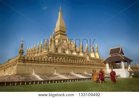 VIENTIANE LAOS - JANUARY 19 2012: Buddhist monk praying and walking around Wat Phra That Luang in Vientiane Lao PDR