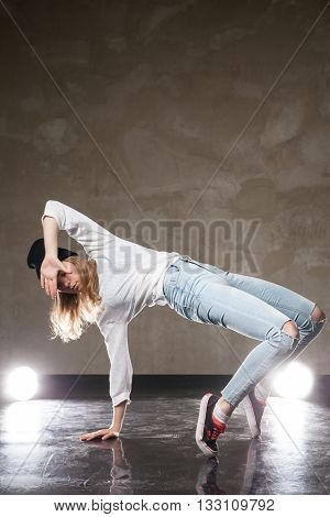 Portrait of young woman performing street dance. Studio shot