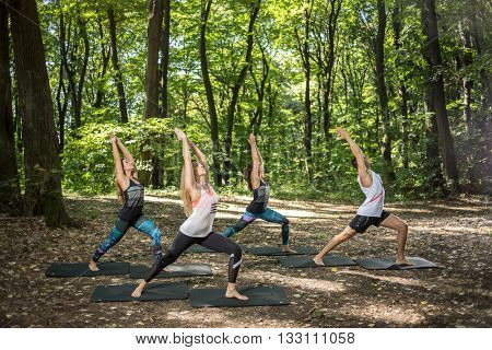 Group flexible athletes doing body balance in beautiful nature