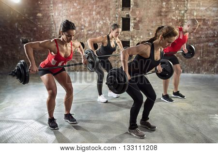 gym group with weight lifting workout body pump