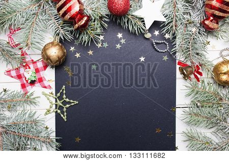 Christmas or New Year decoration background: fur-tree branches, colorful glass balls, decoration and glittering stars on white wooden background, top view, copy space.