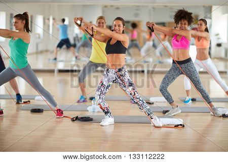 Young women use resistant rubber for exercises in gym