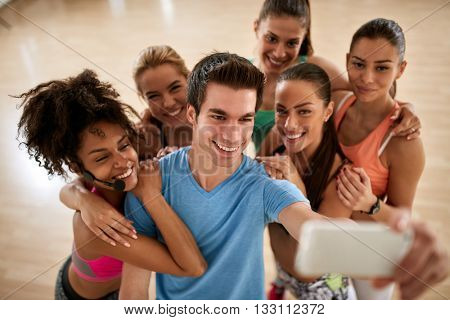 Sports group in fitness gym make group selfie