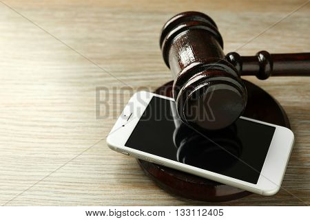 Gavel and smartphone on wooden background