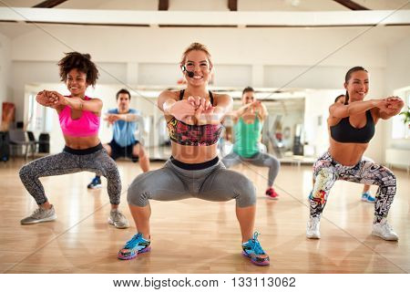 Nice female blond instructor doing exercises for shaping breech and thighs