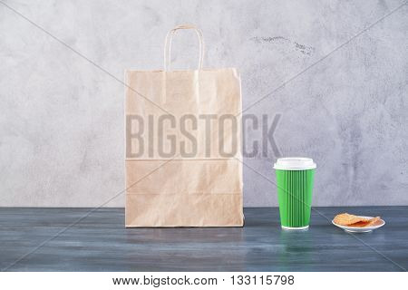 Front view of blank take away food bag saucer with cookies and green coffee cup on wooden surface and concrete background. Mock up