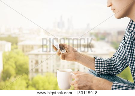 Closeup of man on city background holding coffee cup and using smart phone