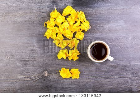 Idea concept with crumpled yellow paper lightbulb and coffee cup on dark wooden desktop