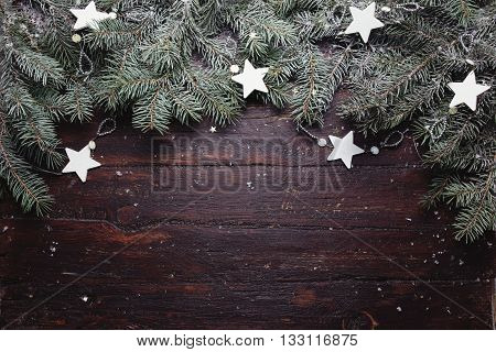 Christmas or New Year background: fur-tree branches, decoration and glittering stars on wooden background, top view, copy space