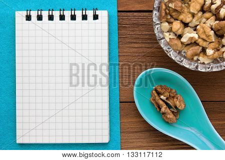 Menu background. Cook book. Recipe notebook with walnuts on a blue background and a wooden board.