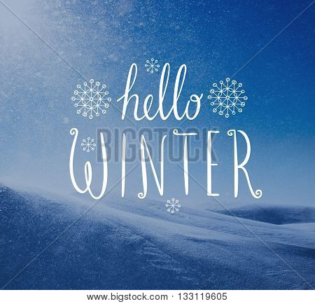 Photo of snowstorm in sunny day with Hello Winter lettering. Winter holidays card.