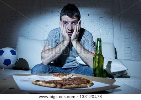 crazy football fan watching soccer game on television nervous and excited suffering stress on sofa couch at home with ball beer bottle and pizza looking anxious and scared of loosing