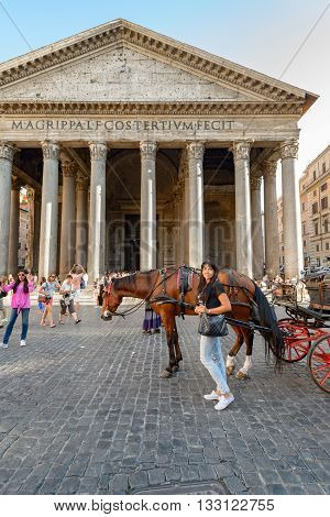 Rome Italy - August 22 2015: a girl near a carriage horse in the Pantheon square in Rome people and Pantheon on backgraund