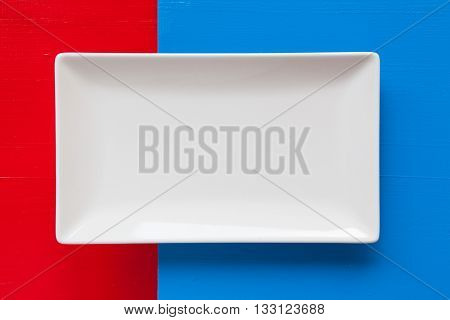 Empty white ceramic dish on over blue and red background rectangle dish
