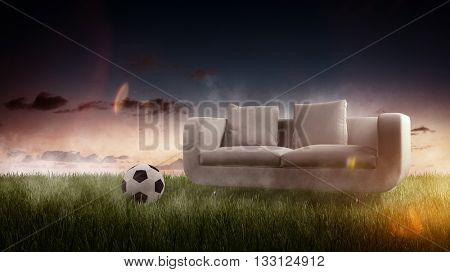 Gray two seat sofa and soccer ball sitting in cut green grass with early evening sky background. 3d Rendering.
