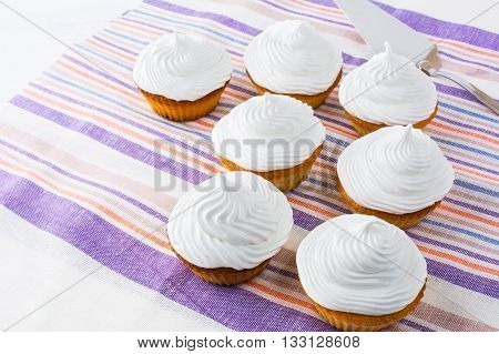 White cupcakes row on the linen napkin. Birthday cupcakes. Homemade cupcake. Sweet cupcake. Sweet dessert. Gourmet cupcakes. Sweet pastry.