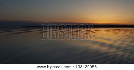Small waves on a lake just after the sun has set in Saskatchewan Canada