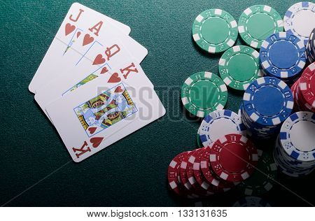 Casino chips and royal flush cards combination on the green table. Poker