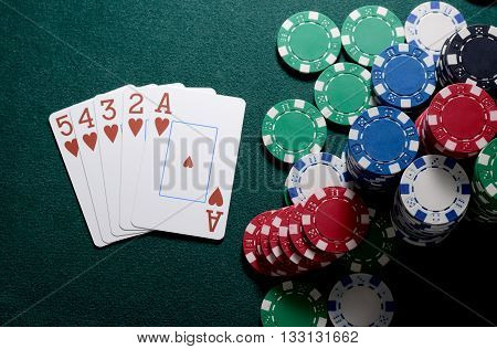 Casino chips and straight flush cards combination on the green table. Poker game.