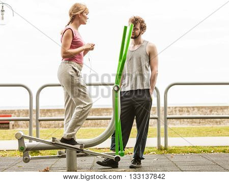 Active woman exercising on elliptical trainer machine and man listening to music. Fit sporty girl in training suit working out at outdoor gym. Sport fitness and healthy lifestyle concept.