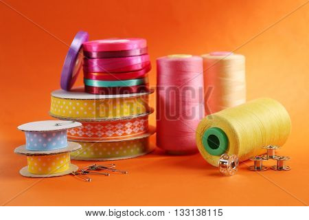 Spools of color ribbons on orange background