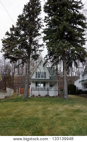 A Victorian home with a wraparound porch and a very steep roof, under the bluff and behind two tall pine trees on Fourth Street in Harbor Springs, Michigan, during December.
