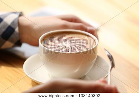 Female hands holding cup of coffee with foam, closeup