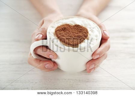Woman holding cup of coffee on wooden background