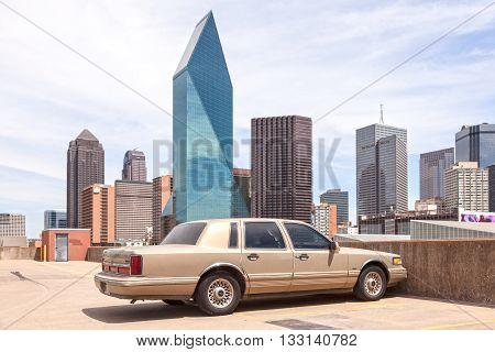 DALLAS USA - APR 7: 1995 Lincoln Town car in front of Dallas Downtown skyscrapers. April 7 2016 in Dallas Texas United States