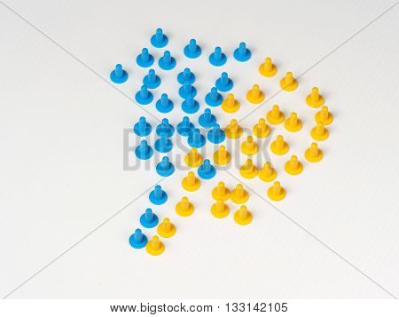 Two groups coming together illustrated by colored plastic board game hats in various colors