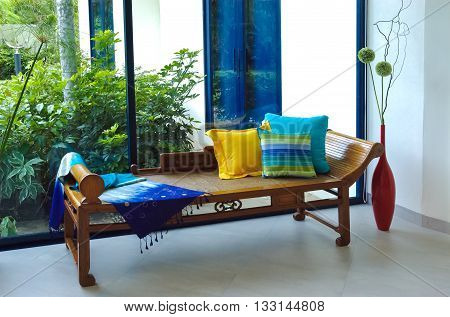 Thai silk fabric and pillows on wooden antique sofa chairs