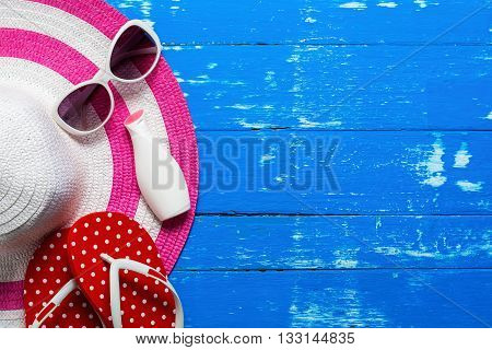 Summer holiday blackground Beach accessories on white wood table Vacation and travel items Red flip flop with sunglasses moisturizer and summer beach hat on wood table