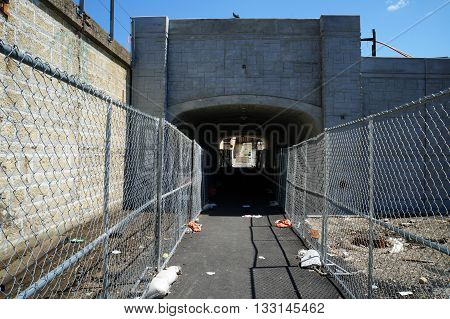 People may walk through a pedestrian viaduct below railroad tracks near the Joliet Union Station in downtown Joliet, Illinois.