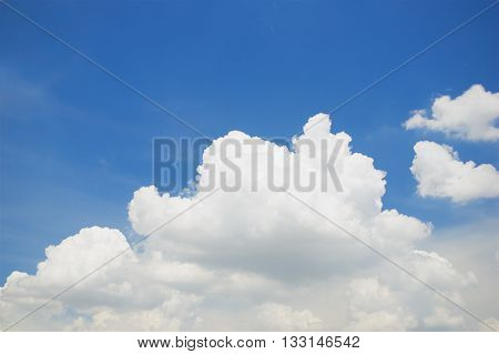 White puffy cumulus cloud on the blue sky as background.