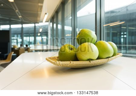 Basket of green apples in lounge or cafeteria