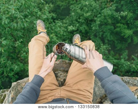 Traveler young man sitting on top of cliff over the summer forest and pouring tea from thermos to cup. Point of view shot
