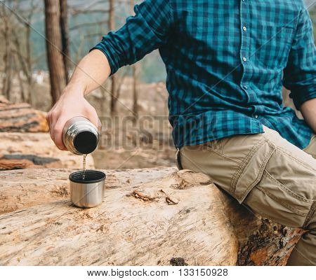 Unrecognizable hiker young man pouring tea from thermos to cup in the forest outdoor