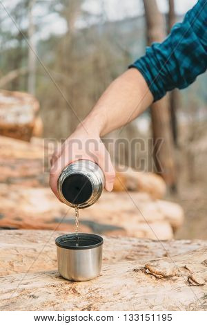 Unrecognizable young man pouring tea from thermos to cup in the forest outdoor close-up view of hand