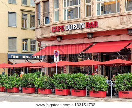 Zurich, Switzerland - 4 September, 2015: Cafe Odeon view from the Limmatquai quay. Cafe Odeon (also Grand Cafe Odeon) is a well-known cafe in Zurich located on the corner of the Limmatquai quay and Raemistrasse street at Bellevue square.