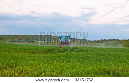 tractor in the agricultural field during the processing of Pesticides